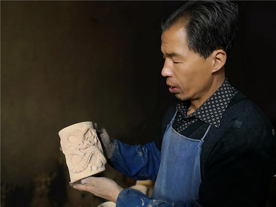 Liu Quan shows one of his works. (Photo by Wei Jianjun for chinadaily.com.cn)