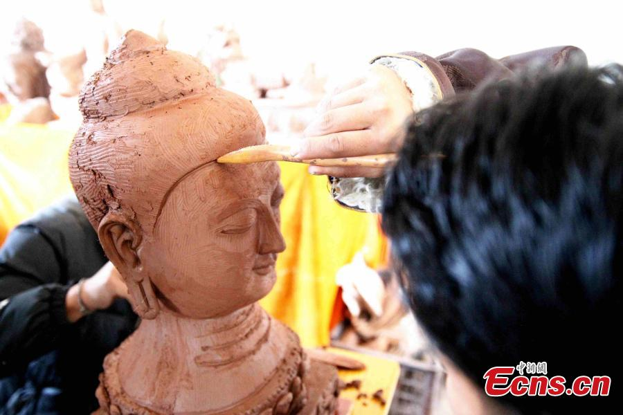 A folk artist creates a clay sculpture in Regong, Tongren County, Huangnan Tibetan Autonomous Prefecture, Qinghai Province, Dec. 25, 2018. Buddhist monks and folk artists carry on the plastic arts of painting thangka and murals, crafting patchwork barbola and sculpting known collectively as the Regong arts, inscribed on the representative list of the UNESCO Intangible Cultural Heritage of Humanity. (Photo: China News Service/Zhang Tianfu)