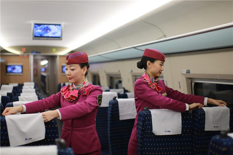 Liu and her colleague tidy up the seat covers during a train stop to prepare for the coming of passengers. (Photo provided to chinadaily.com.cn)