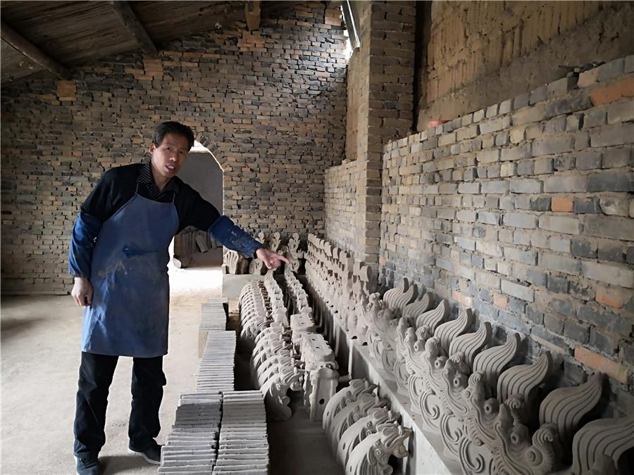 Liu Quan and his sculptures.  (Photo by Wei Jianjun for chinadaily.com.cn)