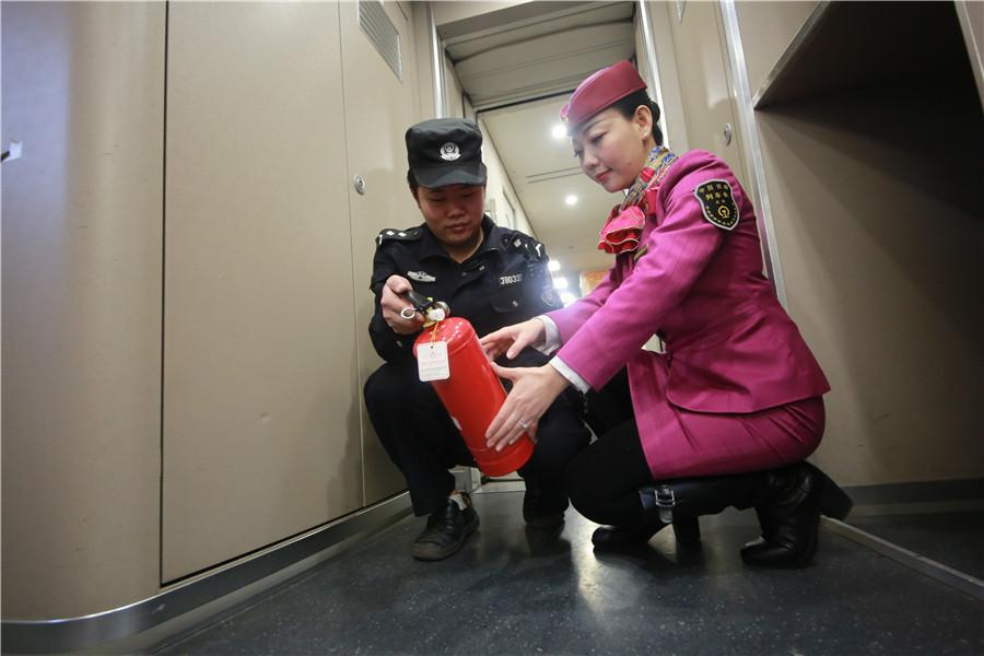 Liu Yuting and a security worker inspect a fire extinguisher on the train.  (Photo provided to chinadaily.com.cn)