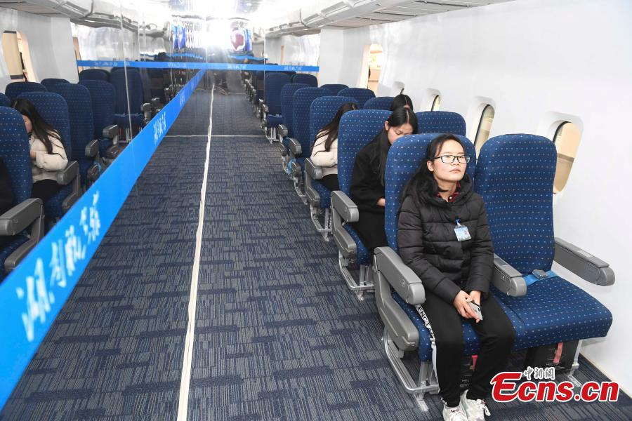 Visitors try out the passenger cabin of an aircraft at the Hunan Aviation Museum at the Changsha Aeronautical Vocational and Technical College in Changsha City, Central China\'s Hunan Province. The museum showcases aviation equipment, aviation technology and culture. It is also the national defense education base of Hunan. (Photo: China News Service/Yang Huafeng)