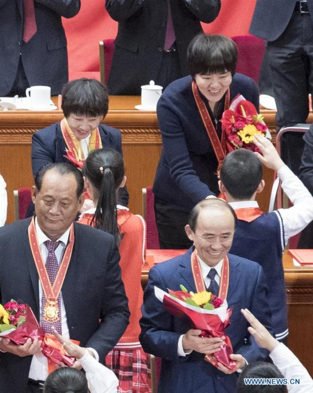 File photo taken on Dec. 18, 2018 shows Lang Ping (top R), head coach of China\'s women volleyball team, accepts bouquets presented by young pioneers during a grand gathering to celebrate the 40th anniversary of China\'s reform and opening-up at the Great Hall of the People in Beijing, capital of China. China\'s first-ever Olympic gold medalist Xu Haifeng, volleyball coach Lang Ping, and former NBA star Yao Ming were among the 100 people selected to be awarded for their contributions to the country\'s reform and opening-up. (Xinhua/Wang Ye)