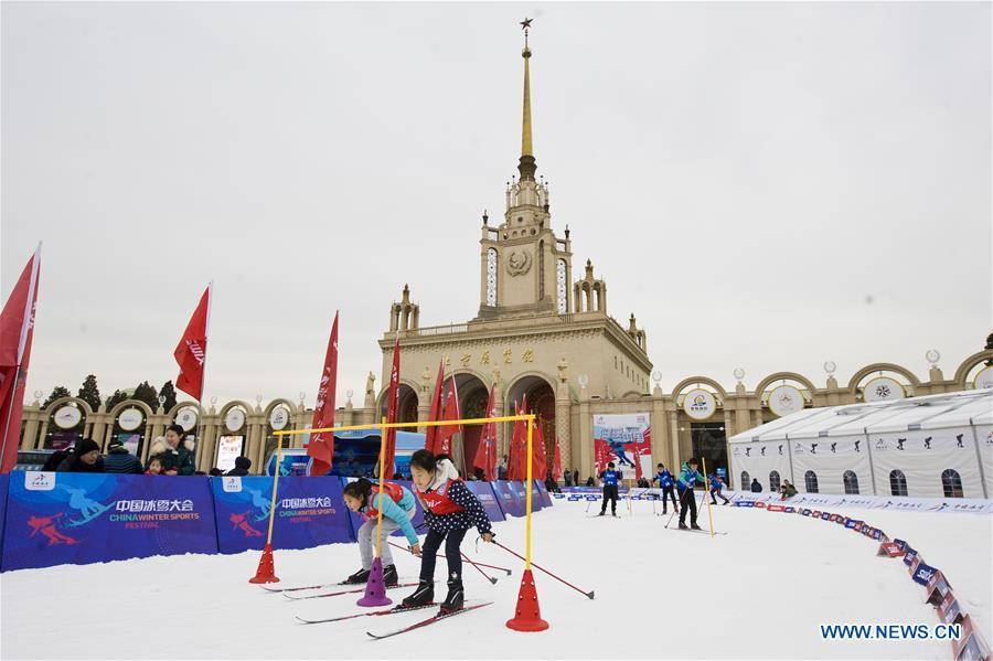 File photo taken on Dec. 22, 2018 shows children ski during the opening ceremony for China Winter Sports Festival in front of Beijing Exhibition Center in Beijing, capital of China. August 8 marked China\'s 10th National Fitness Day, a celebration of the expanded fitness options for the public and ever-greater acceptance of the country\'s national fitness efforts. Winter sports has also seen a big boost in the past year, especially in southern and eastern China.(Xinhua/Wang Jingsheng)