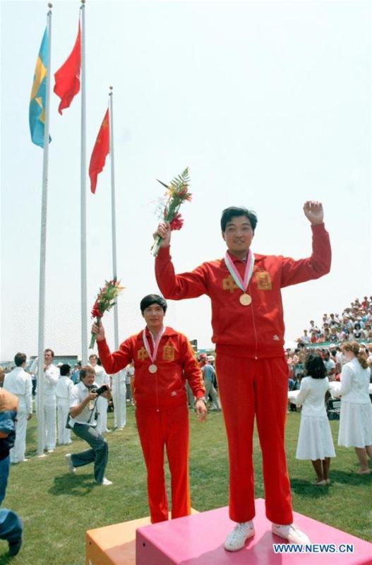 File photo taken on July 29, 1984 shows Chinese shooter Xu Haifeng (R) celebrates on the podium for men\'s pistol at the 10th Olympic Games in Los Angeles, the United States. It was China\'s first Olympic gold medal. China\'s first-ever Olympic gold medalist Xu Haifeng, volleyball coach Lang Ping, and former NBA star Yao Ming were among the 100 people selected to be awarded for their contributions to the country\'s reform and opening-up. (Xinhua/Guan Tianyi)