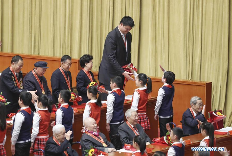 File photo taken on Dec. 18, 2018 shows Yao Ming (top), president of the Chinese Basketball Association (CBA) accepts bouquets presented by young pioneers during a grand gathering to celebrate the 40th anniversary of China\'s reform and opening-up at the Great Hall of the People in Beijing, capital of China. China\'s first-ever Olympic gold medalist Xu Haifeng, volleyball coach Lang Ping, and former NBA star Yao Ming were among the 100 people selected to be awarded for their contributions to the country\'s reform and opening-up. (Xinhua/Yin Gang)