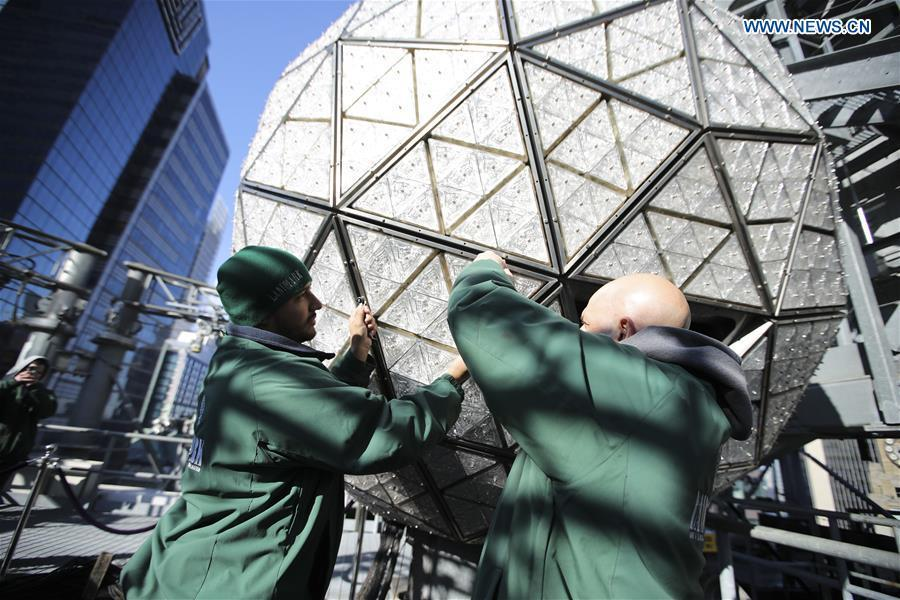 Workers install a panel with new crystal triangles onto the New Year\'s Eve Ball during a ceremony on the roof of the One Times Square building in New York City, the United States, on Dec. 27, 2018. The iconic New Year\'s Eve Ball at New York City\'s Times Square had its latest decoration done on Thursday for the upcoming celebrations. For Times Square 2019, 192 Waterford Crystal triangles introduce the new Gift of Harmony design of small rosette cuts flowing into each other in beautiful harmony. Covered with a total of 2,688 Waterford Crystal triangles, the ball is 12 feet (3.66 meters) in diameter and weighs 11,875 pounds (5386.4 kilograms). (Xinhua/Wang Ying)