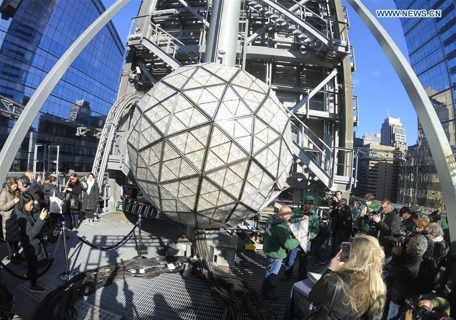 Workers show a panel with new crystal triangles during a ceremony on the roof of the One Times Square building in New York City, the United States, on Dec. 27, 2018. The iconic New Year\'s Eve Ball at New York City\'s Times Square had its latest decoration done on Thursday for the upcoming celebrations. For Times Square 2019, 192 Waterford Crystal triangles introduce the new Gift of Harmony design of small rosette cuts flowing into each other in beautiful harmony. Covered with a total of 2,688 Waterford Crystal triangles, the ball is 12 feet (3.66 meters) in diameter and weighs 11,875 pounds (5386.4 kilograms). (Xinhua/Zhang Mocheng)