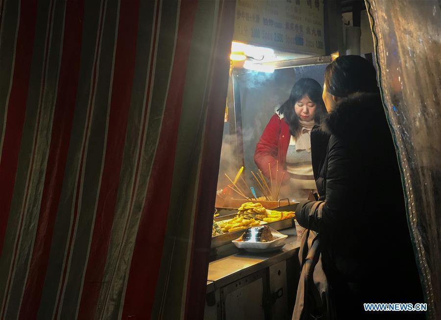 People enjoy hot food at a stall in Seoul, South Korea, Dec. 28, 2018. A cold wave hit the country on Friday, dipping Seoul\'s temperature to minus 19.3 degrees Celsius. (Xinhua/Wang Jingqiang)