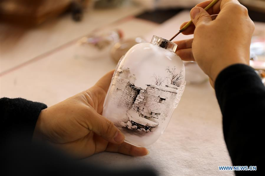 Yin Jianqing shows the inner painting technique at Hebei College of Industry and Technology in Shijiazhuang, north China\'s Hebei Province, Dec. 28, 2018. The college takes intangible cultural heritages such as techniques of pyrograph and inner painting into school courses in recent years. (Xinhua/Liang Zidong)