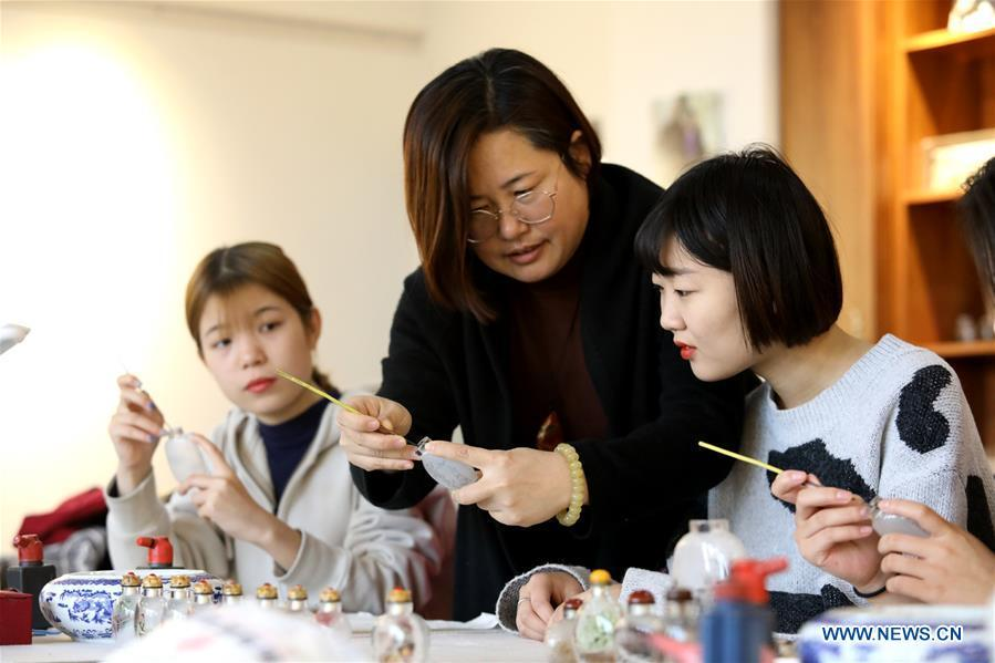 Yin Jianqing (C) teaches students inner painting technique at Hebei College of Industry and Technology in Shijiazhuang, north China\'s Hebei Province, Dec. 28, 2018. The college takes intangible cultural heritages such as techniques of pyrograph and inner painting into school courses in recent years. (Xinhua/Liang Zidong)