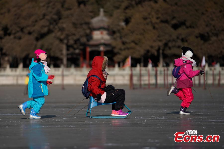 People have fun on the frozen Kunming Lake at the Summer Palace in Beijing, Dec. 30, 2018. With an area of 700,000 square meters, Kunming Lake is the largest natural ice rink in winter in Beijing.The ice rink was open to the public on Sunday. (Photo: China News Service/Du Yang)