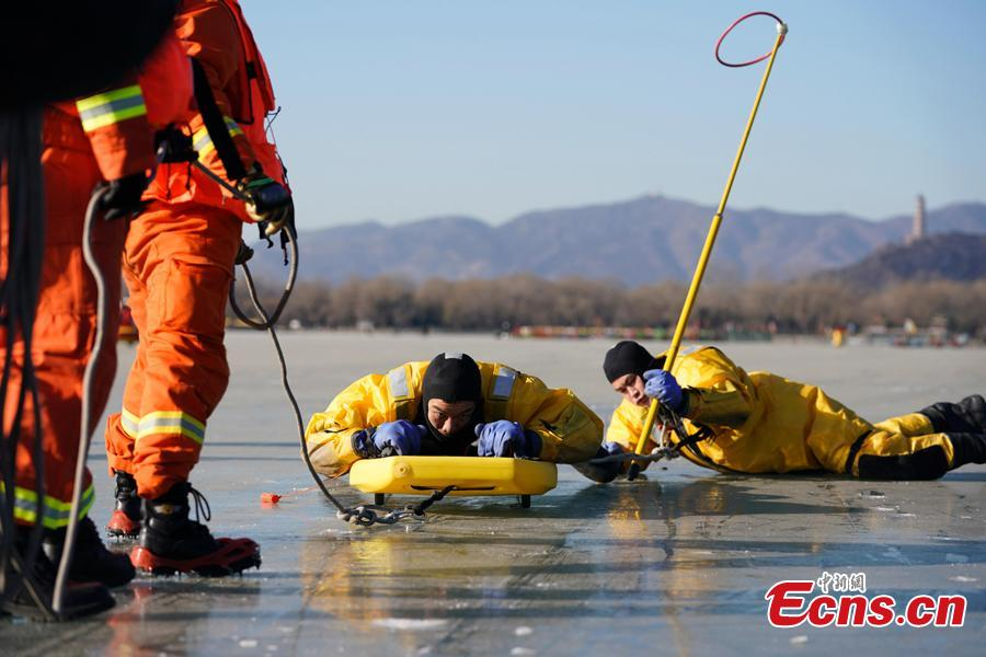 Workers have a rescue drill on the frozen Kunming Lake at the Summer Palace in Beijing, Dec. 30, 2018. With an area of 700,000 square meters, Kunming Lake is the largest natural ice rink in winter in Beijing.The ice rink was open to the public on Sunday. (Photo: China News Service/Du Yang)