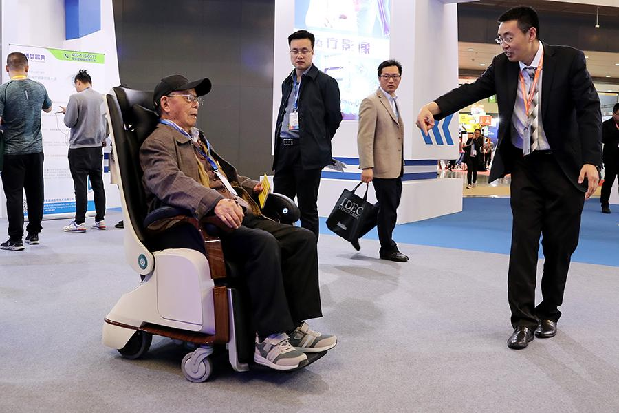 An employee helps a visitor to experience a multi-functional wheelchair designed for elderly healthcare at a fair in Shanghai. (Photo/Xinhua)