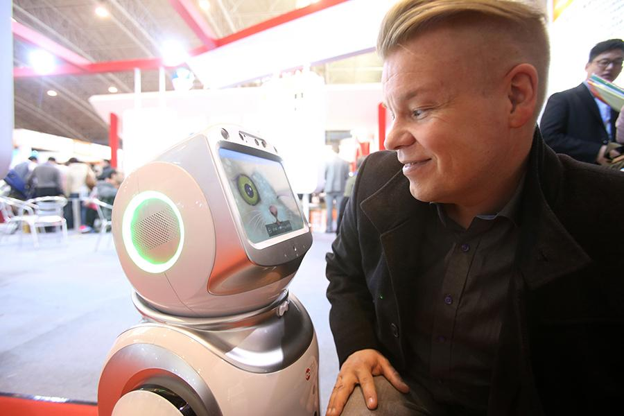 A visitor interacts with a nursing robot at the China International Silver Industry Summit Forum in Beijing. (Photo/Xinhua)