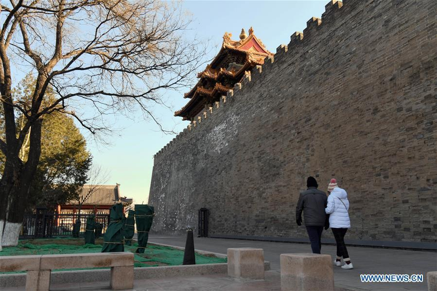 Tourists walk past the wall of the Palace Museum in Beijing, capital of China, Jan. 1, 2019. In order to further enhance visiting experiences and loosen pressure on exits, starting from Jan. 1, 2019, the museum will open the area between its northern Gate of Divine Prowess (Shenwu) and eastern Gate of East Glory (Donghua). (Xinhua/Jin Liangkuai)