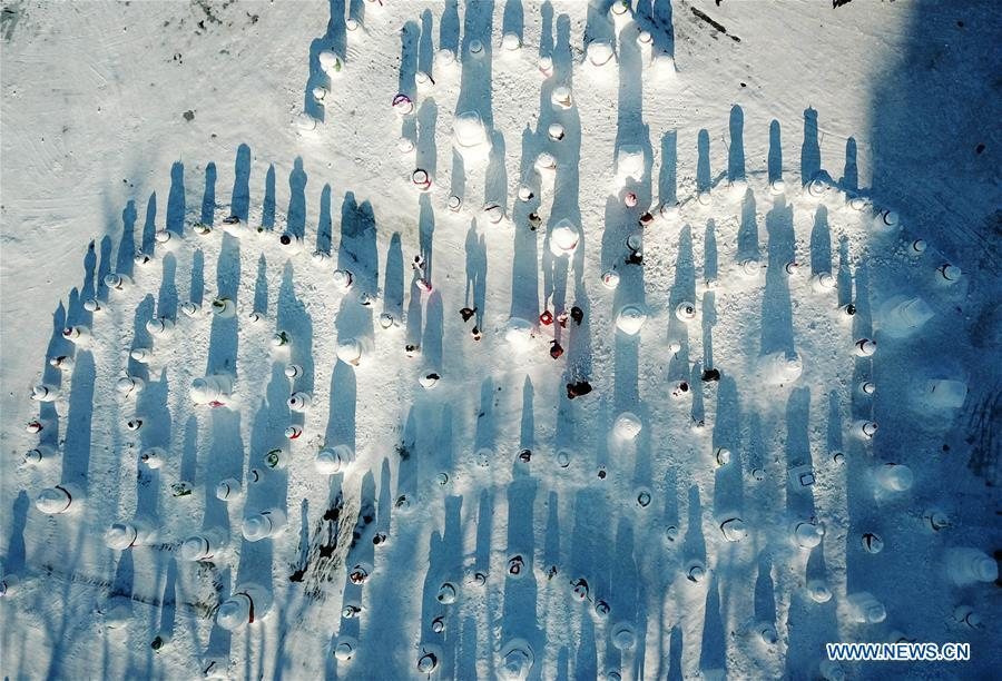 Aerial photo taken on Jan. 2, 2019 shows people viewing snowman sculptures on the riverbank of Songhua River in Harbin, capital of northeast China\'s Heilongjiang Province. Altogether 2,019 cute snowmen were displayed here to greet the year 2019. (Xinhua/Wang Jianwei)
