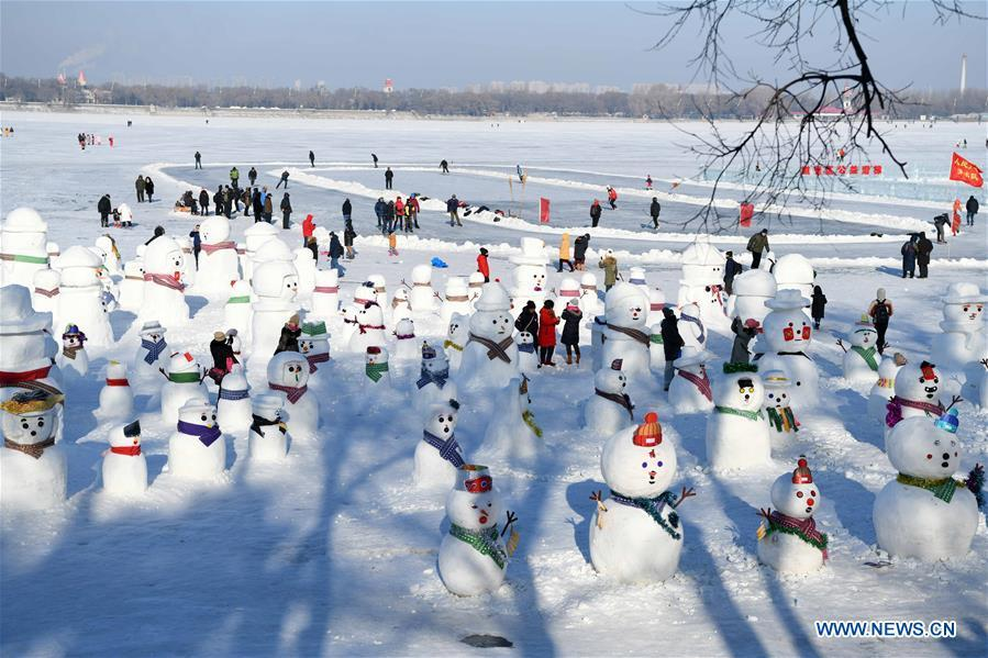 People view snowman sculptures on the riverbank of Songhua River in Harbin, capital of northeast China\'s Heilongjiang Province, Jan. 2, 2019. Altogether 2,019 cute snowmen were displayed here to greet the year 2019. (Xinhua/Wang Jianwei)