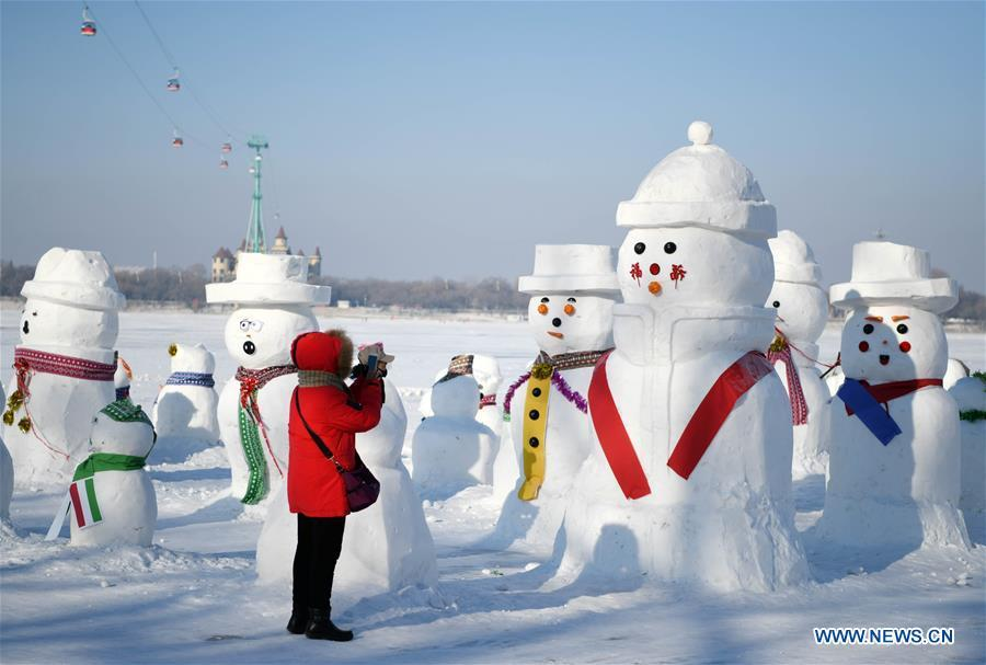A woman takes photos of snowman sculptures on the riverbank of Songhua River in Harbin, capital of northeast China\'s Heilongjiang Province, Jan. 2, 2019. Altogether 2,019 cute snowmen were displayed here to greet the year 2019. (Xinhua/Wang Jianwei)