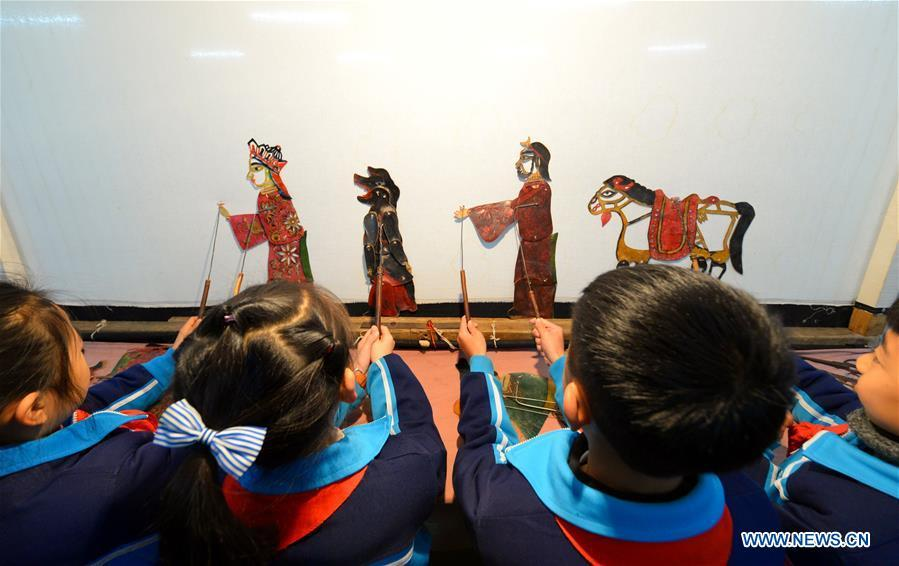 Students perform in a shadow puppetry show at Yangguang Experimental Primary School in Handan City, north China\'s Hebei Province, Dec. 11, 2018. China\'s primary and middle schools have been urged to improve education for all-around student development, according to a directive issued by authorities. Jointly issued by the Ministry of Education and other eight agencies, the circular asked schools to offer courses that are in accord with the national syllabus in terms of their quantity and quality. The enhancement of courses\' difficulty levels and speed at random and in disregard of the curriculum is prohibited, according to the circular. Primary and junior middle schools are not allowed to set up any \
