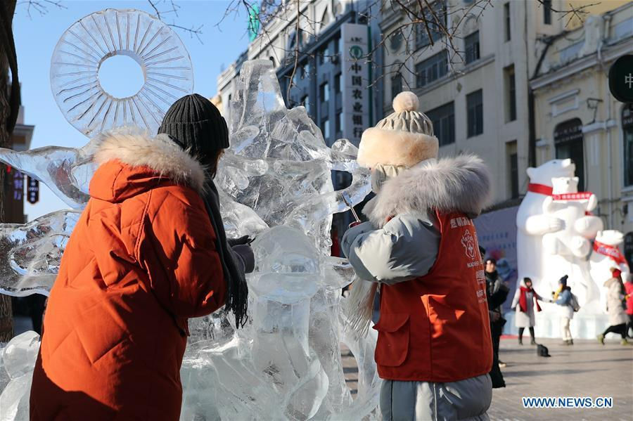 Contestants carve an ice sculpture on the Zhongyang Street during a national college ice sculpture competition in Harbin, capital of northeast China\'s Heilongjiang Province, Jan. 2, 2019. (Xinhua/Cao Jiyang)