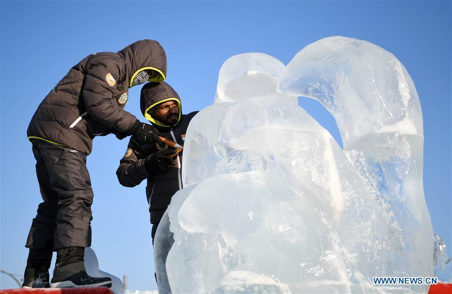 Contestants carve an ice sculpture during an international ice sculpture competition in Harbin, capital of northeast China\'s Heilongjiang Province, Jan. 2, 2019. A total of 16 teams from 12 countries and regions took part in the competition. (Xinhua/Wang Jianwei)