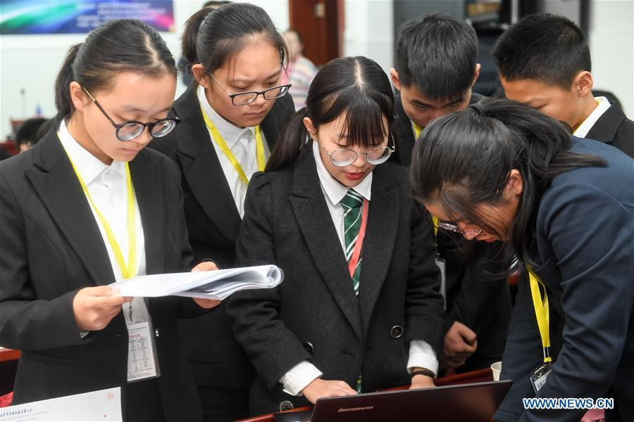 Students discuss during the 8th Model UN conference for middle school students in Hefei, capital of east China\'s Anhui Province, Nov. 17, 2018. China\'s primary and middle schools have been urged to improve education for all-around student development, according to a directive issued by authorities. Jointly issued by the Ministry of Education and other eight agencies, the circular asked schools to offer courses that are in accord with the national syllabus in terms of their quantity and quality. The enhancement of courses\' difficulty levels and speed at random and in disregard of the curriculum is prohibited, according to the circular. Primary and junior middle schools are not allowed to set up any \