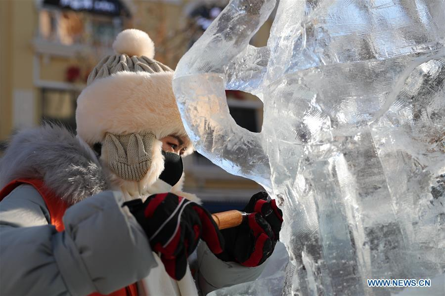 A contestant carves an ice sculpture on the Zhongyang Street during a national college ice sculpture competition in Harbin, capital of northeast China\'s Heilongjiang Province, Jan. 2, 2019. (Xinhua/Cao Jiyang)