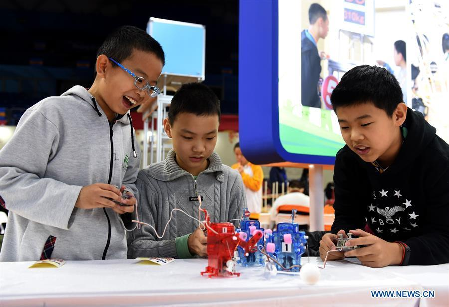 Students manipulate self-assembled robots at the Chongwen Teenager Science and Technology Museum in Dongcheng District of Beijing, capital of China, Nov. 24, 2018. China\'s primary and middle schools have been urged to improve education for all-around student development, according to a directive issued by authorities. Jointly issued by the Ministry of Education and other eight agencies, the circular asked schools to offer courses that are in accord with the national syllabus in terms of their quantity and quality. The enhancement of courses\' difficulty levels and speed at random and in disregard of the curriculum is prohibited, according to the circular. Primary and junior middle schools are not allowed to set up any \
