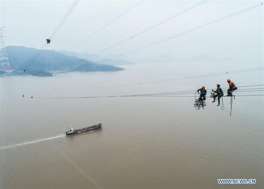 Staff members work on the cables at the site of the giant power supply pylons in Zhoushan, east China\'s Zhejiang Province, Jan. 3, 2019. The two 380-meter-tall pylons carry power cables between Zhoushan\'s Jintang and Cezi islands, a distance of 2,656 meters. The new pylon project is a part of a new ultra-high voltage power line project between cities of Zhoushan and Ningbo. (Xinhua/Xu Yu)