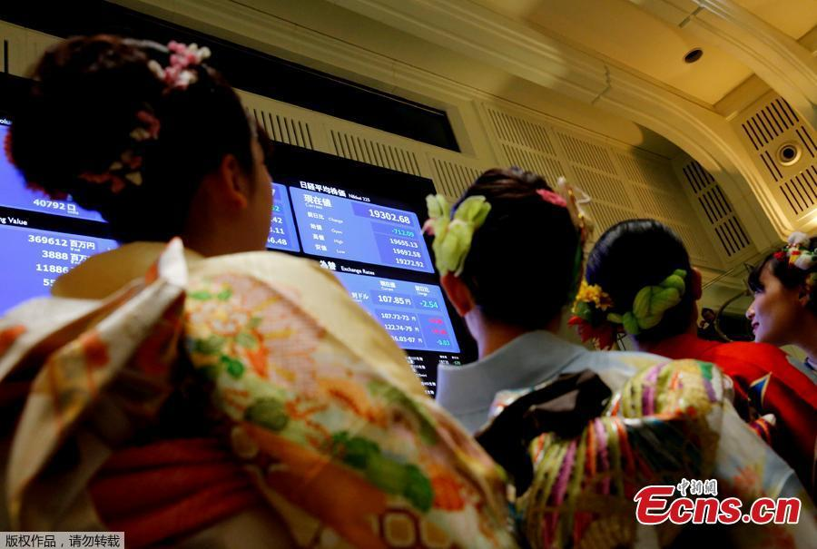 Women, dressed in ceremonial kimonos, pose in front of an electronic board showing stock prices after the New Year opening ceremony at the Tokyo Stock Exchange (TSE), held to wish for the success of Japan\'s stock market, in Tokyo, Japan, January 4, 2019. (Photo/Agencies)