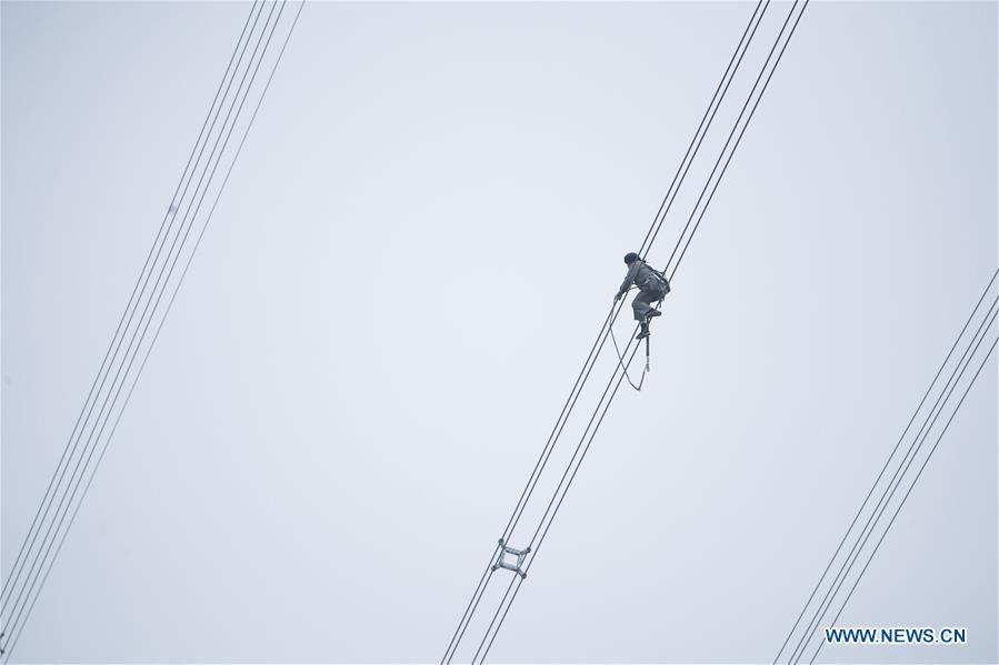 A staff member works on the cables at the site of the giant power supply pylons in Zhoushan, east China\'s Zhejiang Province, Jan. 3, 2019. The two 380-meter-tall pylons carry power cables between Zhoushan\'s Jintang and Cezi islands, a distance of 2,656 meters. The new pylon project is a part of a new ultra-high voltage power line project between cities of Zhoushan and Ningbo. (Xinhua/Xu Yu)