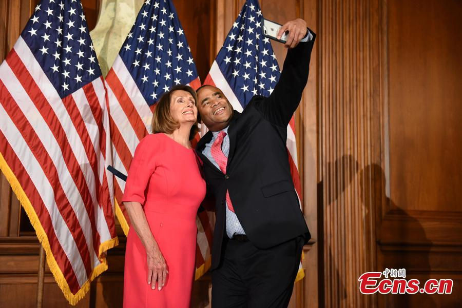 A member of the House of Representatives poses with Speaker of the House Nancy Pelosi (D-Calif.) during the opening session of the 116th Congress in Washington, U.S., January 3, 2019.(Photo: China News Service/Chen Mengtong)