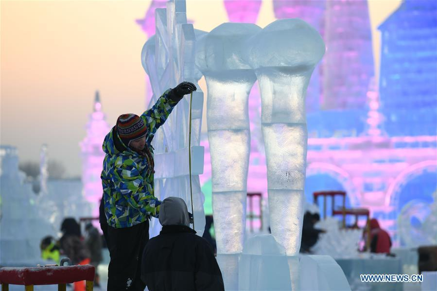 Contestants carve an ice sculpture during an international ice sculpture competition in Harbin, capital of northeast China\'s Heilongjiang Province, Jan. 3, 2019. (Xinhua/Wang Song)