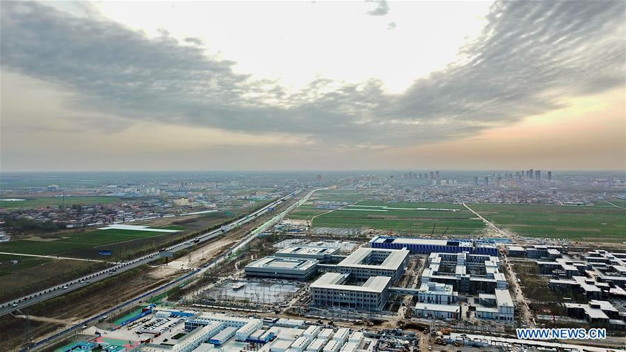 Aerial photo taken on March 29, 2018 shows the construction site of the Xiongan public services center in Xiongan New Area, north China\'s Hebei Province. China\'s central authorities have approved the 2018-2035 master plan for Xiongan New Area, stressing that its creation is significant to high-quality development and the building of the modern economic system. The plan was approved by the Central Committee of the Communist Party of China (CPC) and the State Council. The master plan is the fundamental guideline for the development, construction and management of the Xiongan New Area and should be strictly implemented, according to the approval released on Wednesday. The plan also lists overall development goals for the new area. By 2035, Xiongan will basically develop into a modern city that is green, intelligent and livable, with relatively strong competitiveness and harmonious human-environment interaction. (Xinhua/Mu Yu)