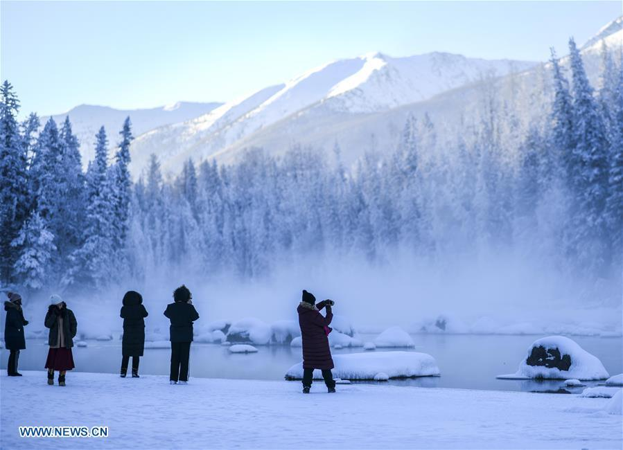People take photos of scenery near the Kanas Lake in Kanas, northwest China\'s Xinjiang Uygur Autonomous Region, Jan. 2, 2019. Kanas scenic spot attracts lots of visitors in winter with its pure snow scenery and various entertainment. (Xinhua/Zhao Ge)