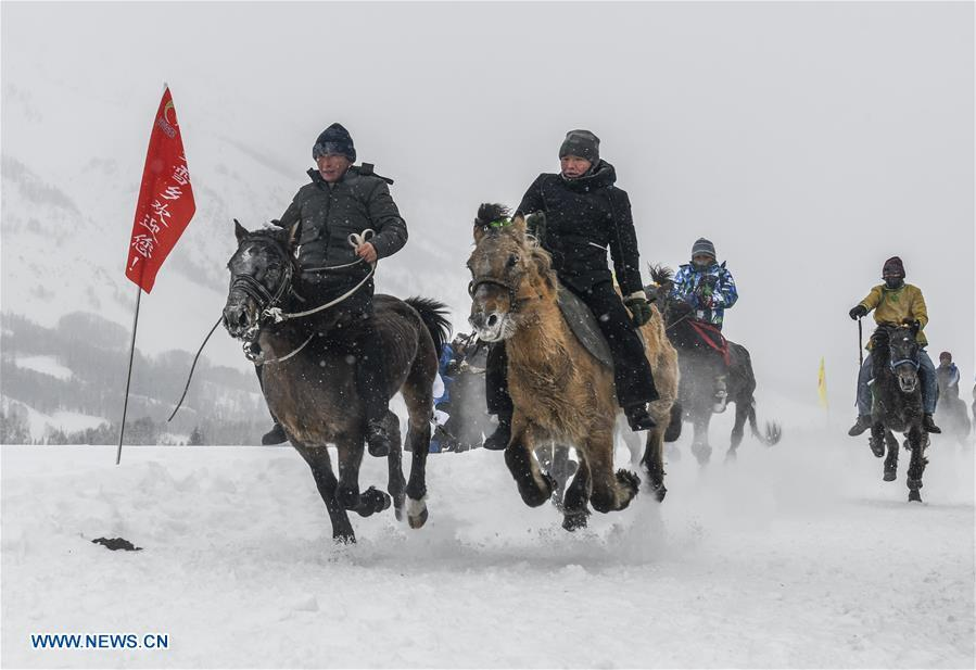 Local residents perform horse riding in snow in Hom scenic area of Kanas, northwest China\'s Xinjiang Uygur Autonomous Region, Jan. 1, 2019. Kanas scenic spot attracts lots of visitors in winter with its pure snow scenery and various entertainment. (Xinhua/Zhao Ge)