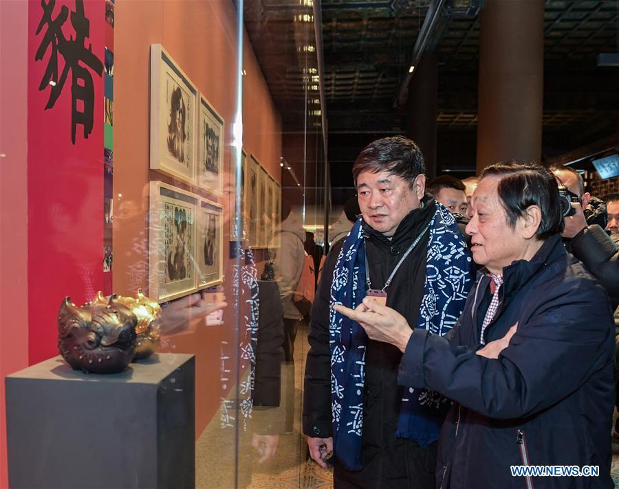 Chinese artist Han Meilin (R) introduces his art works to Shan Jixiang, curator of the Palace Museum, during Han Meilin\'s Chinese Zodiac Art Exhibition in Beijing, capital of China, Jan. 5, 2019. The Chinese Zodiac Art Exhibition, displaying the fine arts of Chinese artist Han Meilin, kicked off in the Palace Museum on Saturday and will last until Feb. 20, 2019. (Xinhua/Li He)
