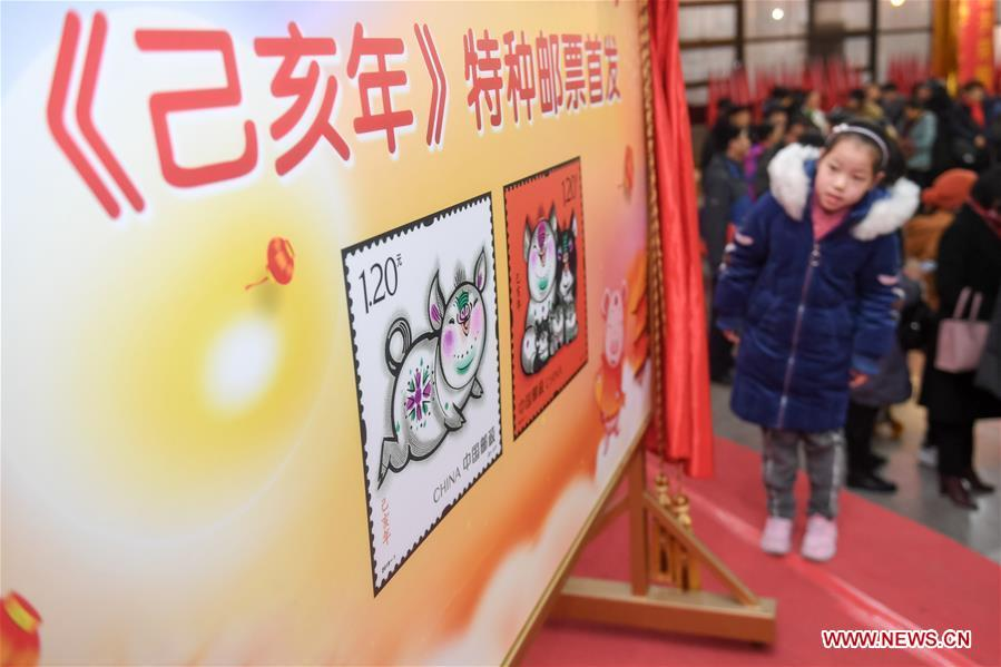 A kid is seen during the issue ceremony of special zodiac stamps for the lunar year of the Pig in Hefei, capital of east China\'s Anhui Province, Jan. 5, 2019. China Post on Saturday issued a set of special zodiac stamps in honor of 2019 Chinese Lunar New Year, or the Year of the Pig. The Year of the Pig starts from Feb. 5, 2019. (Xinhua/Zhang Duan)