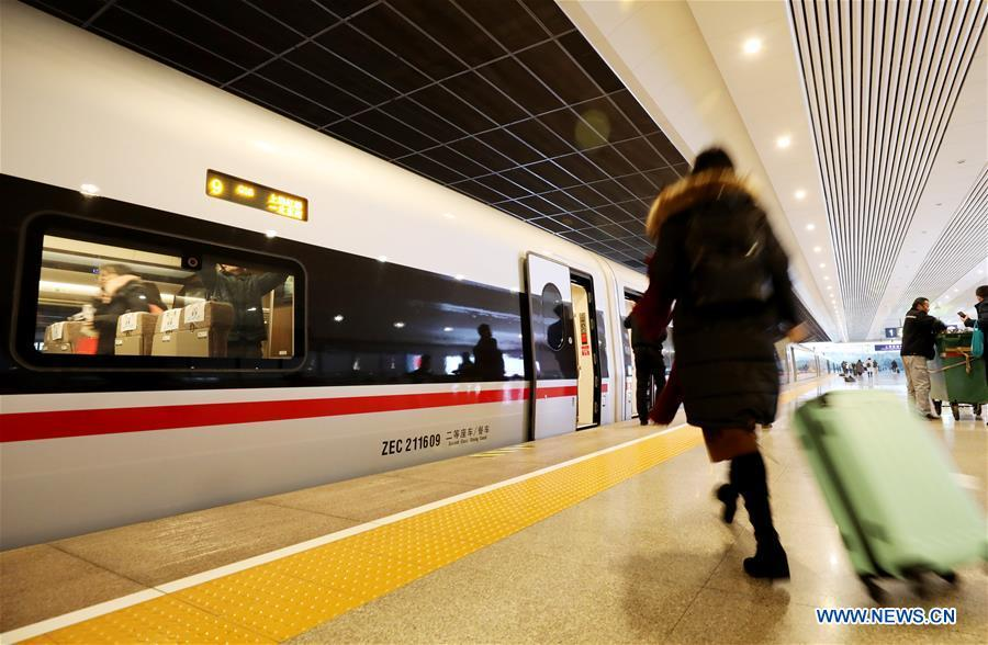 A passenger boards on a new Fuxing bullet train at Shanghai Hongqiao Railway Station in Shanghai, east China, Jan. 5, 2019. A longer Fuxing bullet train started running on the Beijing-Shanghai line Saturday at noon. The new train, with a designed speed of 350 km per hour, has 17 carriages, one carriage longer than the Fuxing trains currently in use. (Xinhua/Fang Zhe)