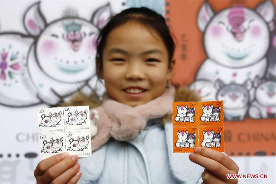 A kid presents special zodiac stamps for the lunar year of the Pig in Huangshan City, east China\'s Anhui Province, Jan. 5, 2019. China Post on Saturday issued a set of special zodiac stamps in honor of 2019 Chinese Lunar New Year, or the Year of the Pig. The Year of the Pig starts from Feb. 5, 2019. (Xinhua/Shi Yalei)