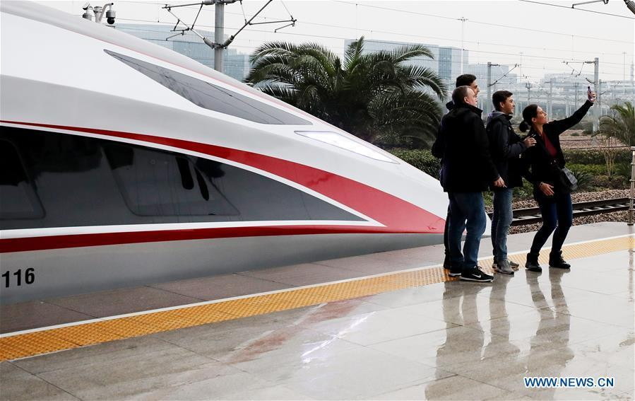 Passengers take selfie with a new Fuxing bullet train at Shanghai Hongqiao Railway Station in Shanghai, east China, Jan. 5, 2019. A longer Fuxing bullet train started running on the Beijing-Shanghai line Saturday at noon. The new train, with a designed speed of 350 km per hour, has 17 carriages, one carriage longer than the Fuxing trains currently in use. (Xinhua/Fang Zhe)