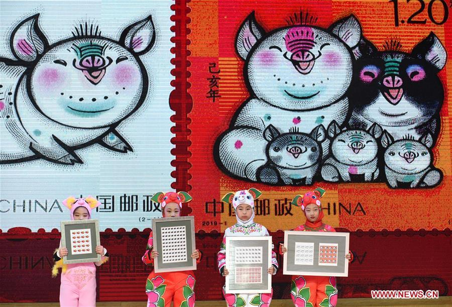 Kids present special zodiac stamps for the lunar year of the Pig in Nanjing, capital of east China\'s Jiangsu Province, Jan. 5, 2019. China Post on Saturday issued a set of special zodiac stamps in honor of 2019 Chinese Lunar New Year, or the Year of the Pig. The Year of the Pig starts from Feb. 5, 2019. (Xinhua/Sun Can)