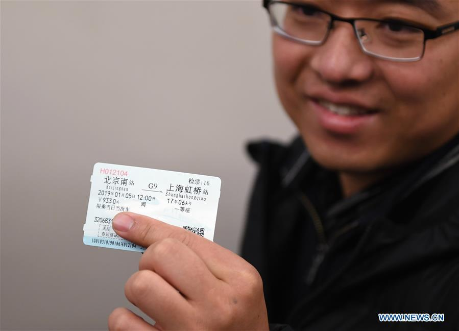 A passenger shows his ticket for a seat in the 17th carriage of a new Fuxing bullet train, at Beijing South Railway Station in Beijing, capital of China, Jan. 5, 2019. A longer Fuxing bullet train started running on the Beijing-Shanghai line Saturday at noon. The new train, with a designed speed of 350 km per hour, has 17 carriages, one carriage longer than the Fuxing trains currently in use. (Xinhua/Zhang Chenlin)
