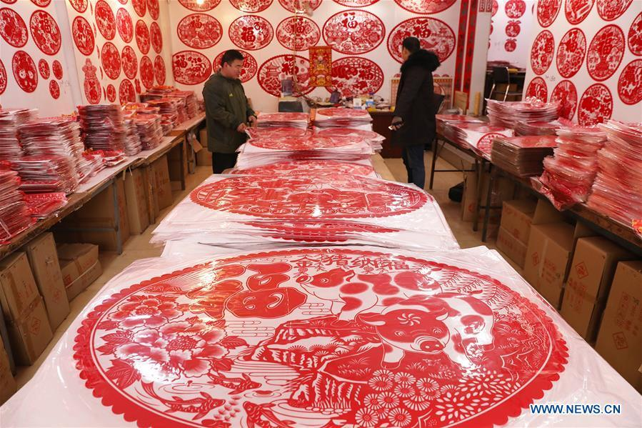 Customers select New Year goods at a market in Shijiazhuang, north China\'s Hebei Province, Jan. 6, 2019. People are busy buying decorations such as Spring Festival couplets and lanterns to greet the upcoming Lunar New Year. (Xinhua/Liang Zidong)