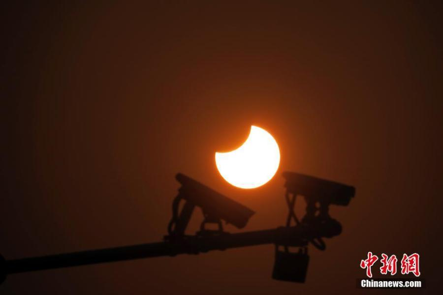 A partial solar eclipse is observed next to security cameras in Jingshan Park in Beijing, Jan. 6, 2019. (Photo: China News Service/Sun Zifa)