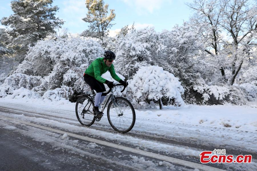 A cyclist rides his bike on the snow-covered Mount Parnitha, near Athens, Greece, Jan. 4, 2019. An elderly woman was found dead and two men were missing after blizzards hit parts of Greece, police officials said on Saturday. (Photo/Agencies)