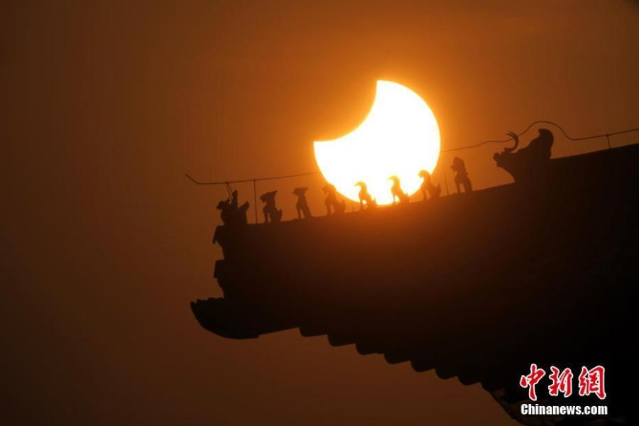 A partial solar eclipse is observed next to the Forbidden City in Beijing, Jan. 6, 2019. (Photo: China News Service/Sun Zifa)