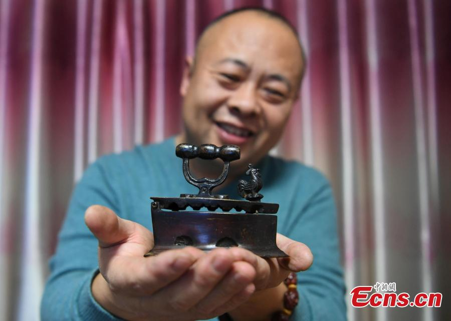 Teng Yongshan of Jilin City in Jilin Province shows his collection of irons - a collection he began in 2000. The former teacher has collected more than 40 irons that were made during the Jin (1115-1234) to Qing Dynasties (1368-1644) and in the early Republic period. Some of the irons were imported into China, including some from Japan and Germany. (Photo: China News Service/Zhang Yao)