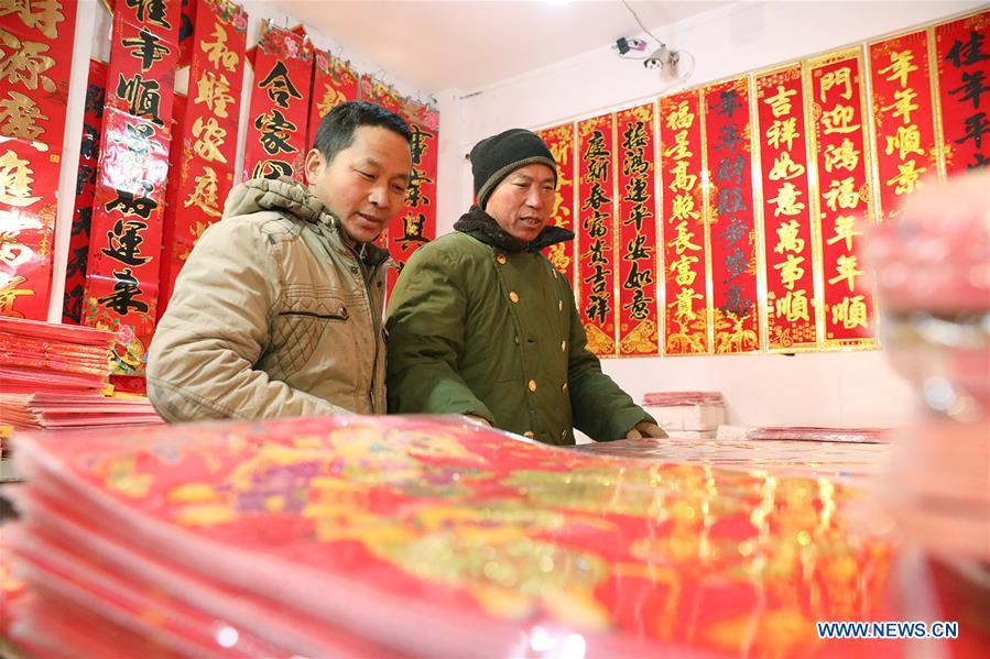 A seller arranges newly arrived Spring Festival couplets at a market in Shijiazhuang, north China\'s Hebei Province, Jan. 6, 2019. People are busy buying decorations such as Spring Festival couplets and lanterns to greet the upcoming Lunar New Year. (Xinhua/Liang Zidong)
